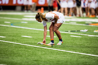 An Orange player bends down to pick up a stick.